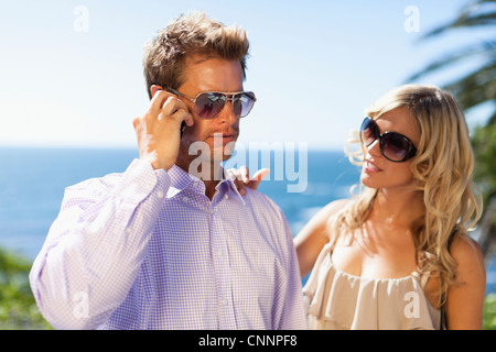 Man ignoring girlfriend for cell phone - Stock Photo