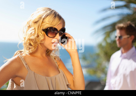 Woman ignoring boyfriend for cell phone - Stock Photo