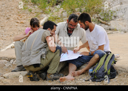 Researchers looking at map in desert, Socotra, Yemen, march - Stock Photo