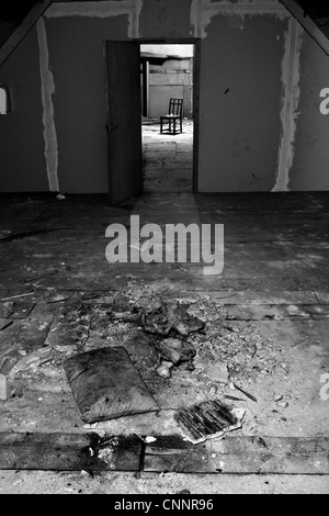 An old derelict room through a room. Possibly used by squatters. Could be an old interrogation room. - Stock Photo