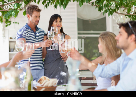 Friends toasting each other outdoors - Stock Photo
