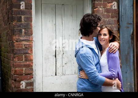Portrait of Young Couple Embracing in Alleyway - Stock Photo