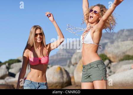 Women in bikinis playing on beach - Stock Photo