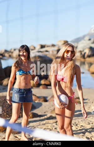 Smiling women playing beach volleyball - Stock Photo