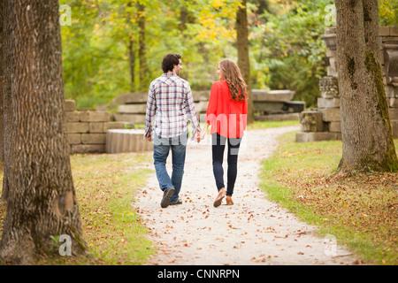 Backview of Young Couple Walking through Park in Autumn, Ontario, Canada - Stock Photo