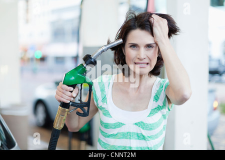 Frustrated woman pumping gas into hair - Stock Photo