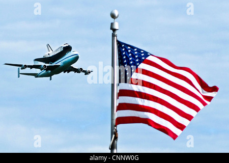 The space shuttle Discovery attached to its 747 transport passes over a US flag during a flyover of the nation's - Stock Photo