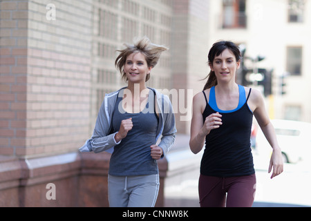 Women running together on city street - Stock Photo