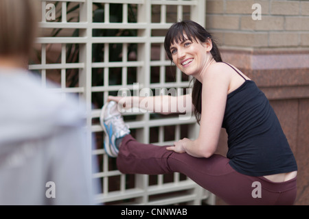 Woman stretching together on city street - Stock Photo