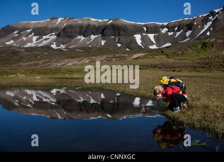 Hiker admiring reflection in still pond - Stock Photo