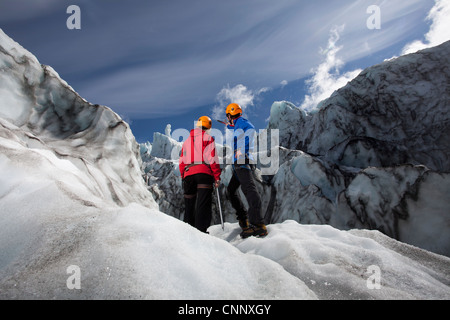 Hikers admiring glacial landscape - Stock Photo