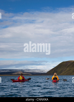 Couple rowing canoes in still lake - Stock Photo