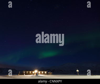 Lit building in snowy field - Stock Photo