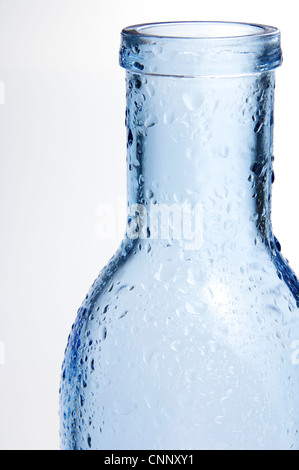 foreground of a blue glass bottle with splashes of water and white background - Stock Photo
