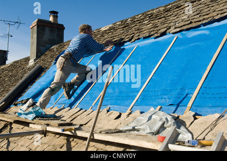 Man tiling roof with slate rock - Stock Photo
