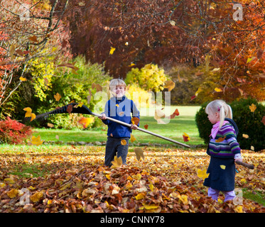 Children raking fall leaves - Stock Photo