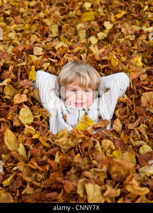 Boy laying in pile of fall leaves - Stock Photo