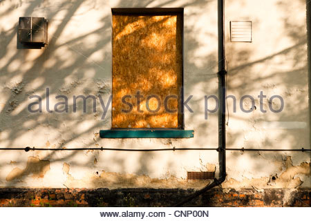 Sunlight through a tree casting shadows on an old disused building with a boarded up window, England, UK - Stock Photo