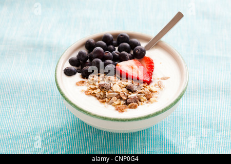 Bowl of muesli with yoghurt, strawberries and blueberries for healthy breakfast - Stock Photo