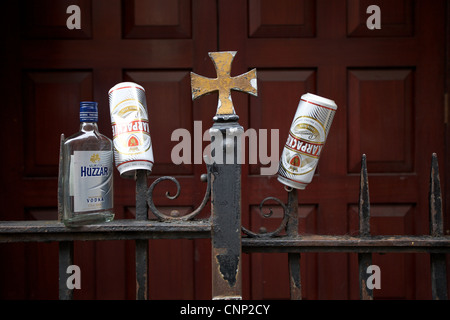 Empty cans and bottles of alcohol left on gates of a church in Dublin city centre. - Stock Photo