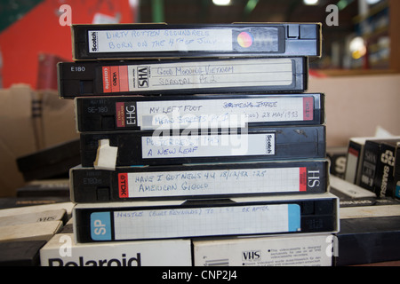 A pile of VHS video cassettes on sale at a flea market. - Stock Photo