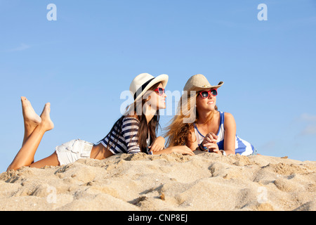 girls laying in sand on summer vacation - Stock Photo