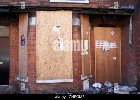 boarded up windows on a damaged vandalised house in Belfast Northern Ireland UK - Stock Photo