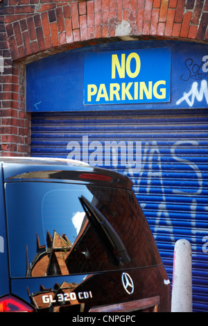 mercedes suv parked across no parking sign in front of garage entry in Belfast Northern Ireland UK - Stock Photo