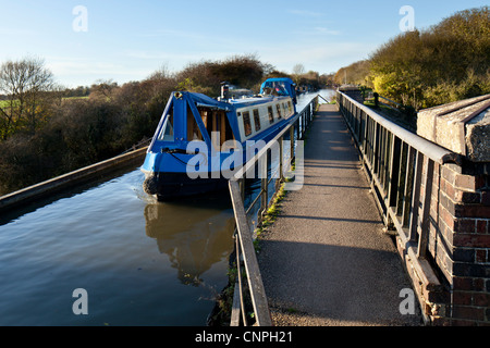 A canal boat crosses the Cosgrove Iron Trunk Aqueduct on the Grand Union Canal near to Milton Keynes, UK - Stock Photo