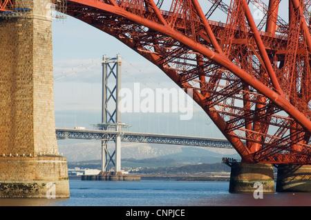 The Forth Road Bridge viewed through an arch of the Forth Rail Bridge, near Edinburgh, Scotland. - Stock Photo