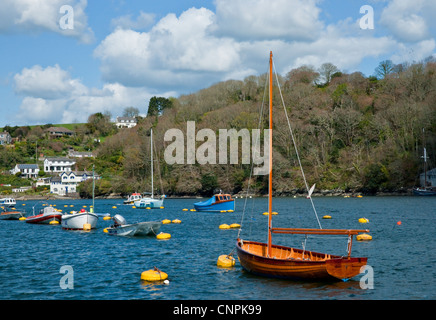 A small wooden sailing boat moored on the river in amongst other small boats. - Stock Photo