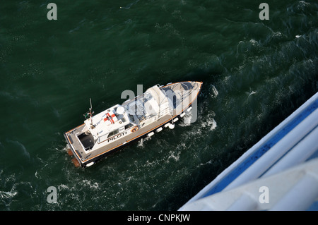 View from above of sea pilot boat guiding cruise ship. - Stock Photo