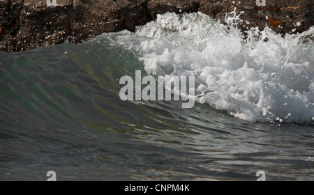 Waves in motion breaking on the shore line in between rocks. - Stock Photo