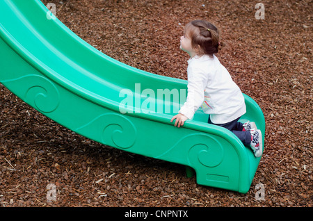 A child plays on a green slide in a playground. - Stock Photo