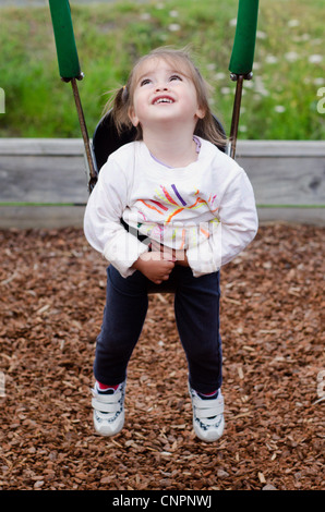 A child looks up and swings on a swing and plays in a playground. - Stock Photo