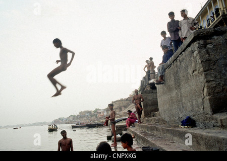 Indian boy jumping on the Ganges river at the ancient Indian city of Benares (Varanasi), Uttar Pradesh, India. - Stock Photo