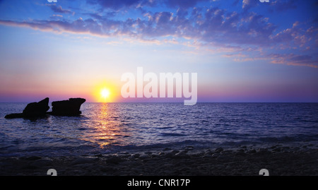 Beautiful sunset on the beach, seascape with calm ocean and rocks in the blue water - Stock Photo