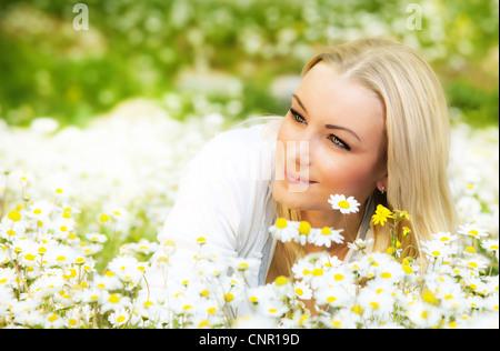 Beautiful woman enjoying daisy field, nice female lying down in the meadow of flowers, pretty girl relaxing outdoor, - Stock Photo