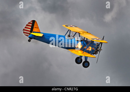 Boeing PT17 Stearman bi-plane American training aircraft with flames coming from the engine exhaust pots - Stock Photo