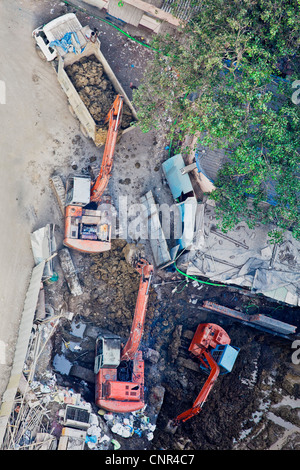 Any orientation of construction site in Mumbai, India, aerial view of mechanical diggers at work - Stock Photo