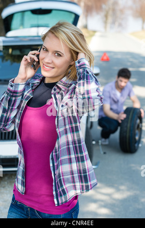 Car trouble woman calling road assistance man change broken wheel - Stock Photo