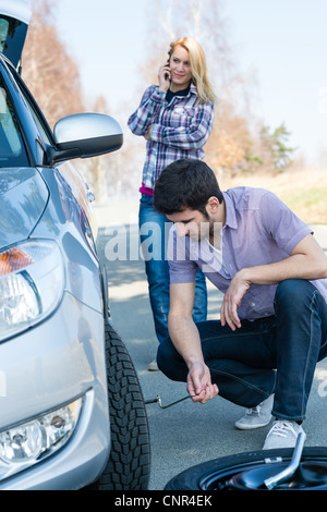 Car wheel defect man change puncture tire woman calling assistance - Stock Photo