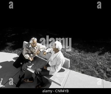 two elderly ethnic men sitting on a bench talking - Stock Photo