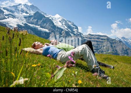 Couple Sitting on Mountain Side, Bernese Oberland, Switzerland