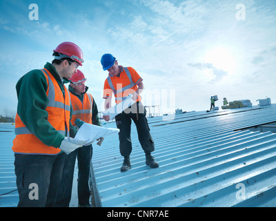 Workers reading blueprints on roof - Stock Photo