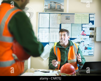 Construction workers talking in office - Stock Photo