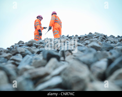 Workers standing on quarry rock pile - Stock Photo