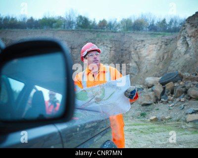 Workers reading blueprints in quarry - Stock Photo
