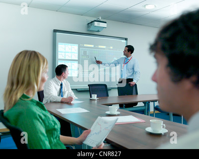 Businessman using projection in meeting - Stock Photo