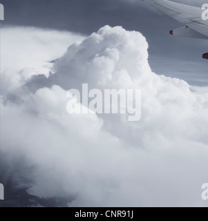 Aerial view of clouds and airplane wing - Stock Photo